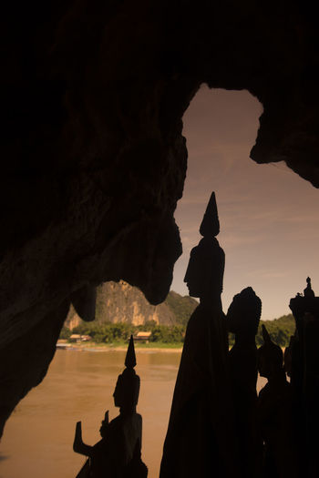 Silhouette buddha statues at pak ou caves by river during sunset