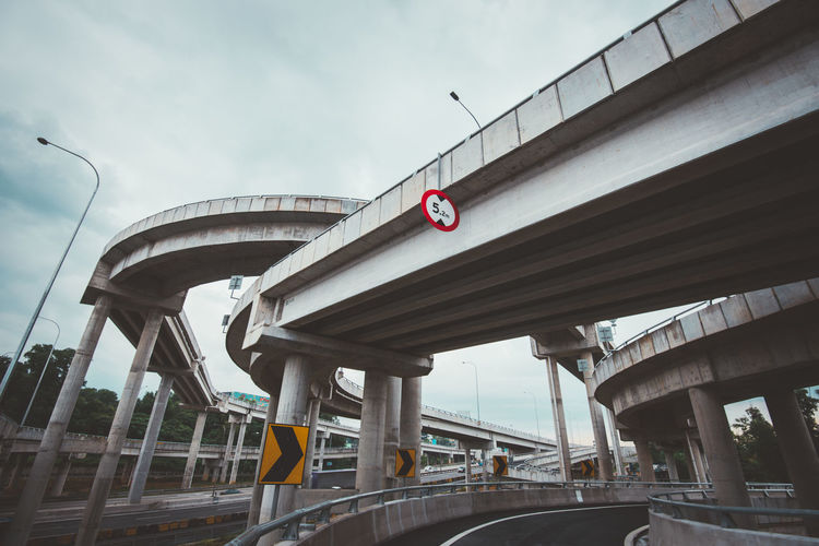 Bridges In City Against Cloudy Sky