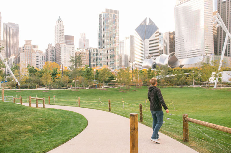 Man on footpath at millennium park against modern buildings in city