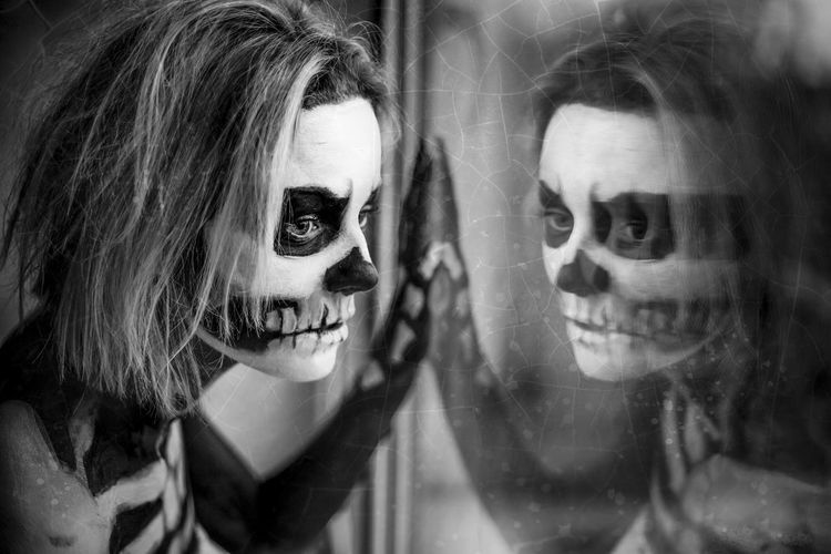 Close-up portrait of a woman in skeleton body paint with reflection on window