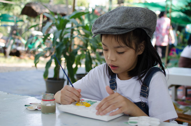 Close-up of girl making paintings on table