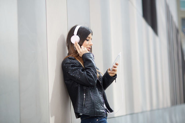 Young woman using mobile phone while standing against wall