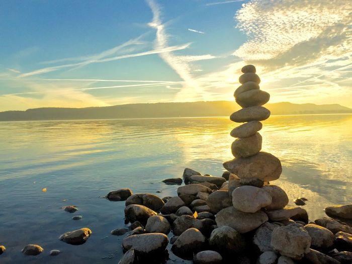 Stack Of Stones Against Calm Sea At Sunset
