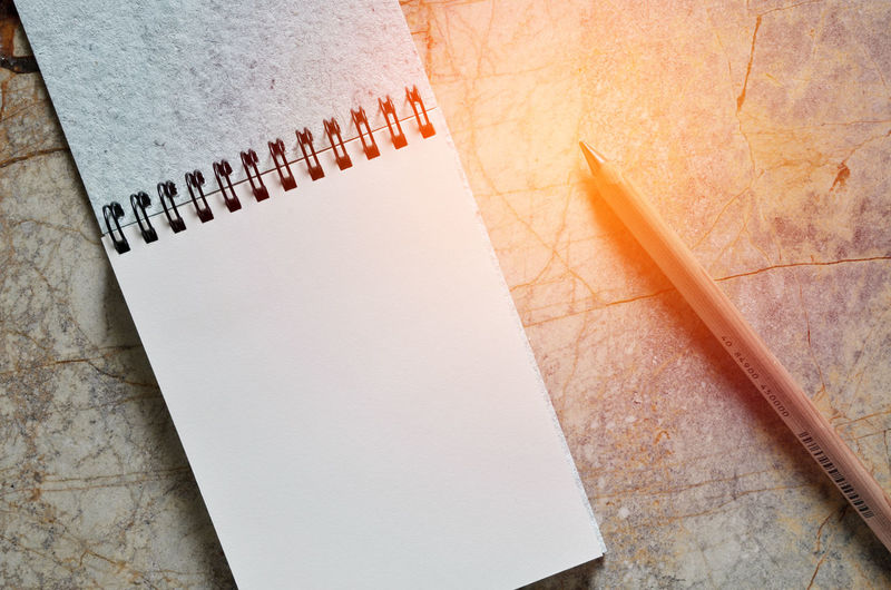 Close-up of open notebook and pencil on cracked floor