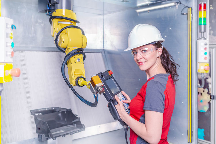 Portrait of smiling technician working on machinery in factory