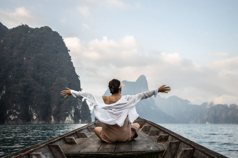 An asian woman in a white shirt sits in front of a boat trip in thailand. amazing thailand.