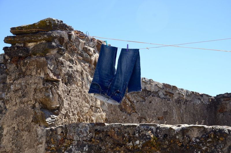 Blue jeans hanging on the wal Jeans Hanging Sky Low Angle View Clothing Drying Clothesline Laundry No People Outdoors Blue Laundry Textile