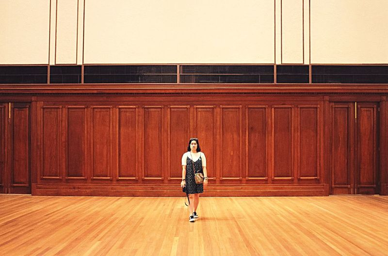 Full length of young woman standing on hardwood floor against wooden wall in room
