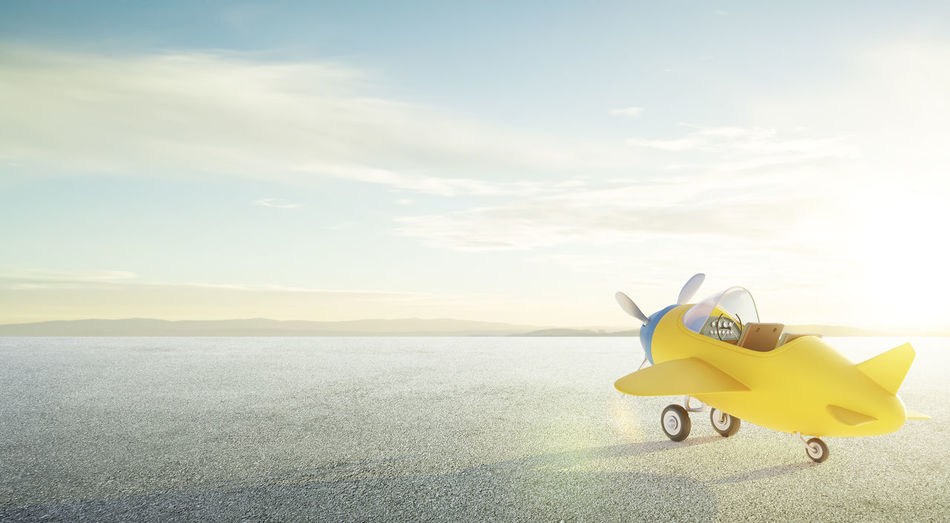Yellow toy airplane on sea against sky