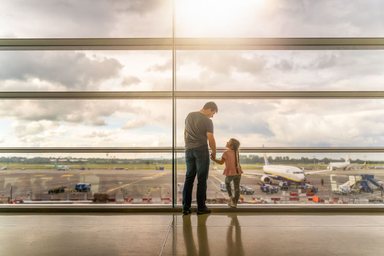 People at airport against sky seen through glass window