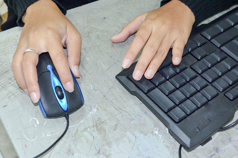 Cropped Hands Of Woman Using Computer On Table