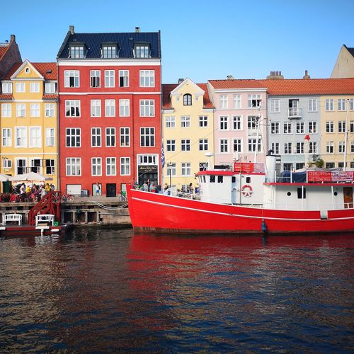 Boats moored in canal by buildings against sky in city