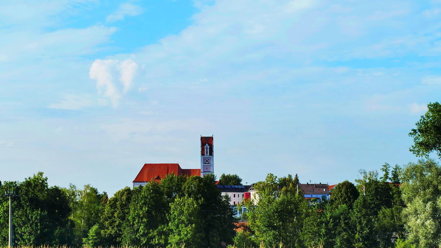 Bavarian Church Bavarian Landscape Church Houses Architecture Blue Building Building Exterior Built Structure Church Architecture Cloud - Sky Day Green Color Growth Nature No People Outdoors Plant Pollution Red Sky Smoke Stack Sunlight Tree
