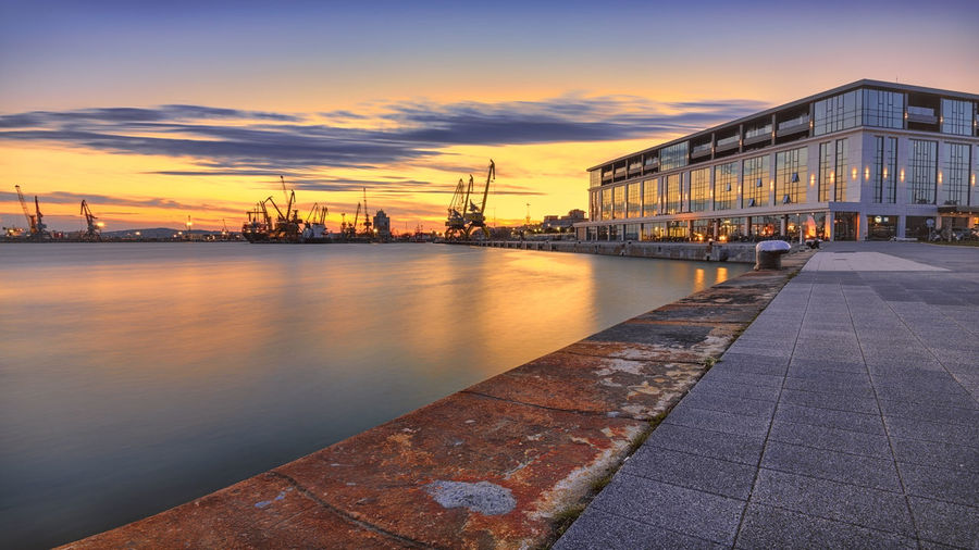 View of buildings at waterfront during sunset