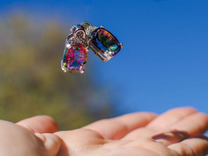 Cropped hand under earrings against sky