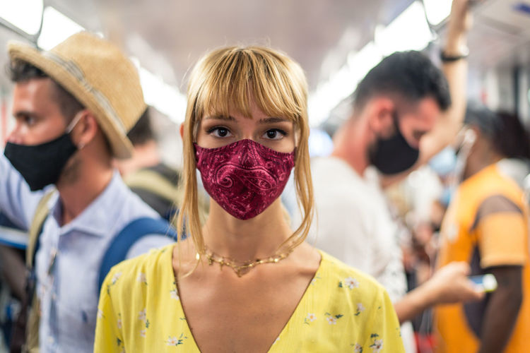 Portrait of woman wearing mask standing in bus