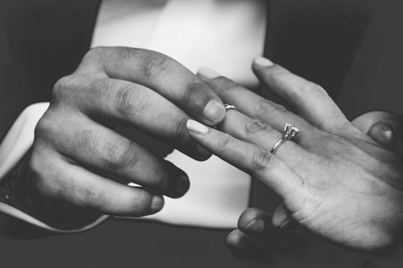 Midsection of groom exchanging ring with bride during wedding