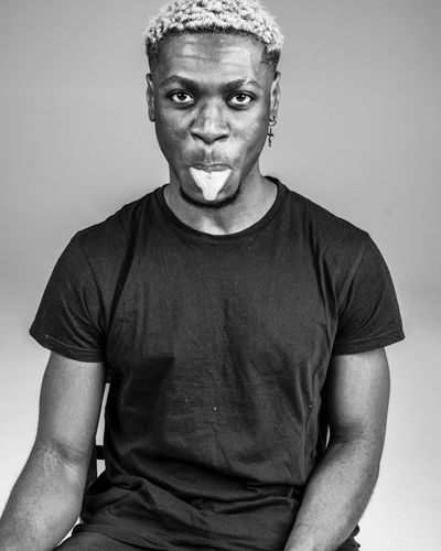 Portrait of young man sticking out tongue against gray background