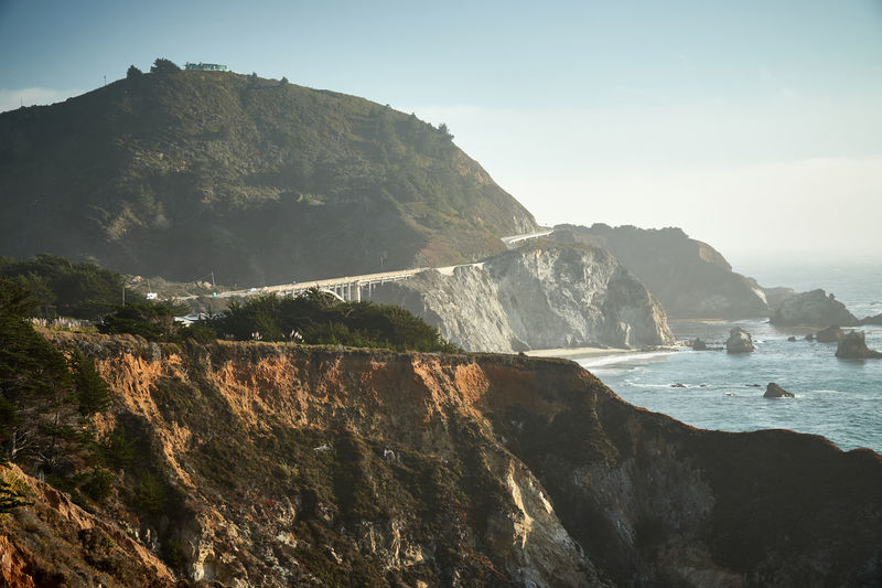 Bixby Creek bridge at pacific coast highway at low sun Pacific Coast, Highway Travel Leisure Activity Lifestyles California Dreaming California Coast Landscape Bixby Bridge Sky Mountain Beauty In Nature Rock Scenics - Nature Nature Sea Land No People Clear Sky Tranquility Outdoors Beach Rock Formation Cliff Water