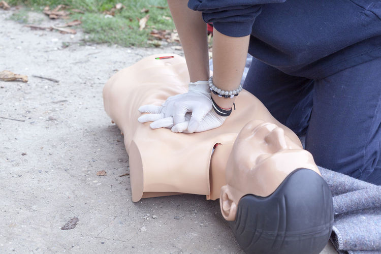 Midsection of paramedic performing cpr on mannequin