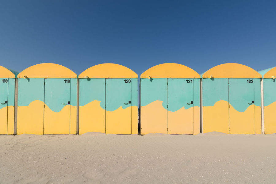 French beach cabins, Dunkerque. Arched Beach Beach Cabins Beach Life Blue Clear Sky Colors Dunkerque Beach France In A Row Multi Colored North Sea Outdoors Repetition Sand & Sea Side By Side Tranquility Yellow Yellow Color Yellow Waves The Essence Of Summer Paint The Town Yellow