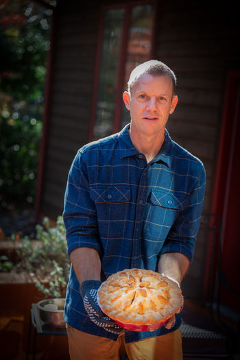 Portrait of mature man holding sweet pie outside house