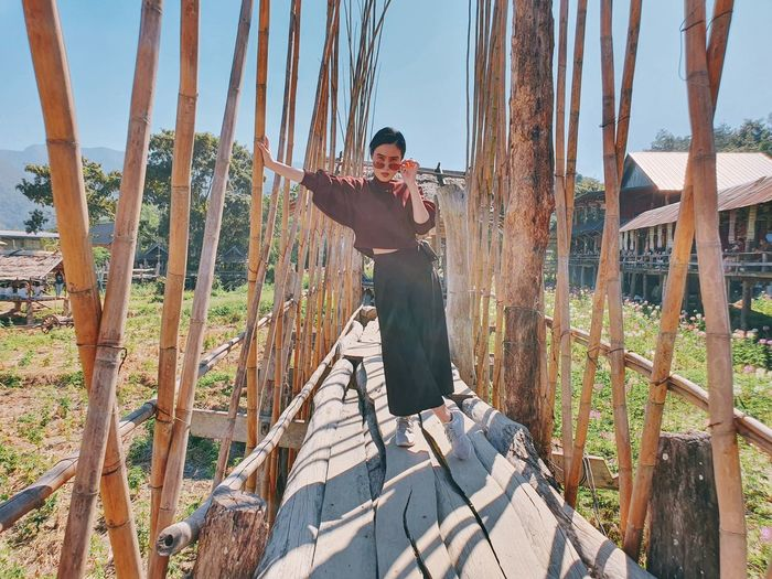 Full length of asian woman standing on bamboo bridge in the garden, thailand