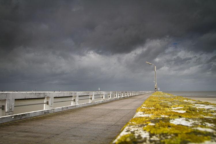 Vanishing pier against cloudy sky
