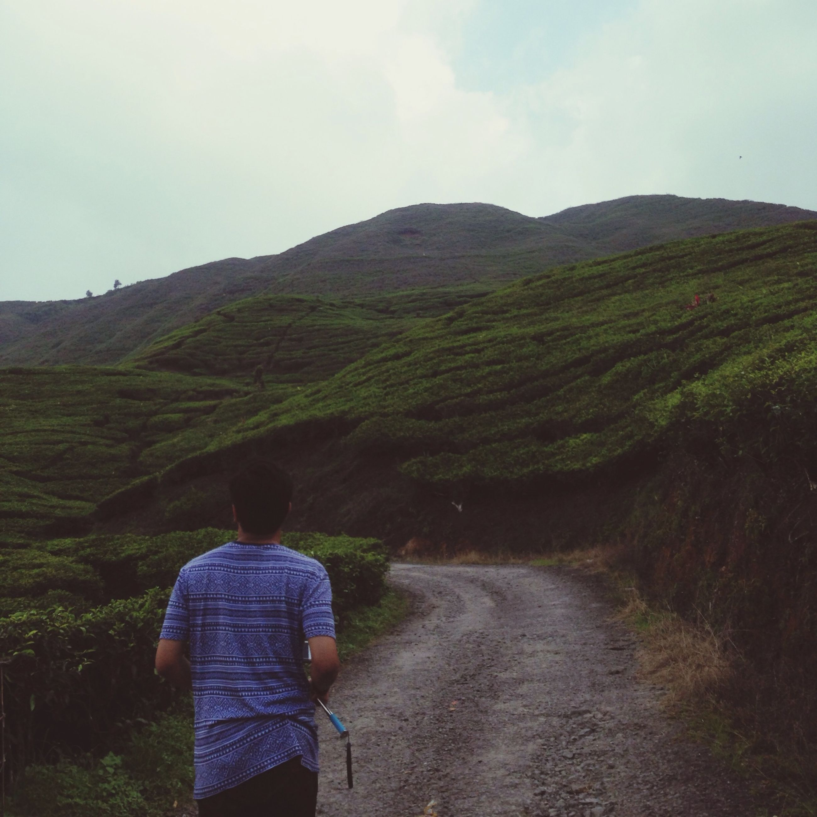 lifestyles, mountain, leisure activity, rear view, landscape, casual clothing, men, tranquility, sky, tranquil scene, grass, standing, nature, scenics, beauty in nature, person, hiking, walking