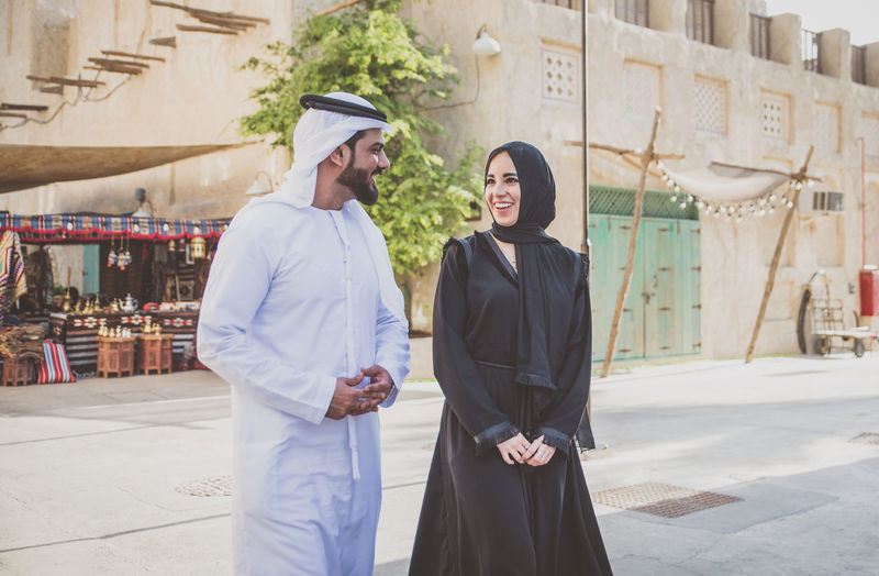 Smiling couple talking while walking on street in town