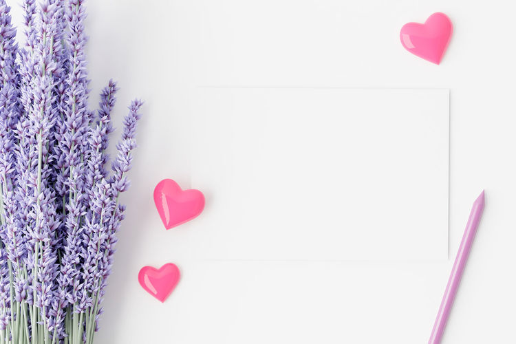 Close-up of heart shape with pink flowers against white background