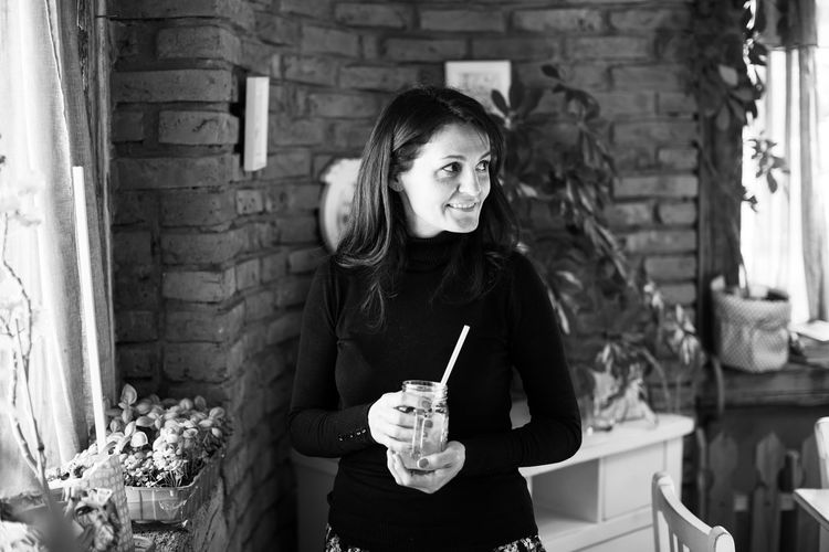 Smiling woman with drink standing against brick wall at home