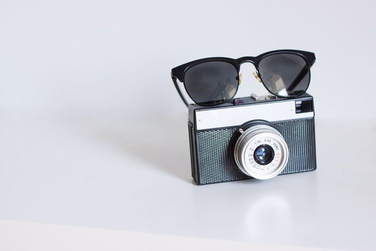 Close-Up Of Camera And Sunglasses On White Table