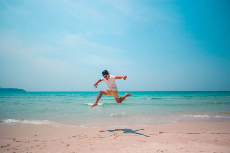 Full length of young man jumping at beach against blue sky