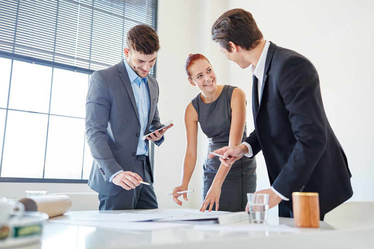 Smiling business people making strategies in office