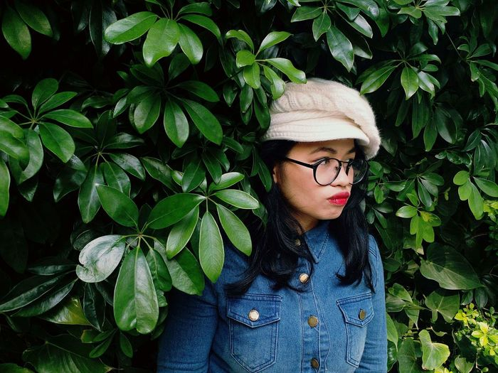 Young woman wearing hat against plants