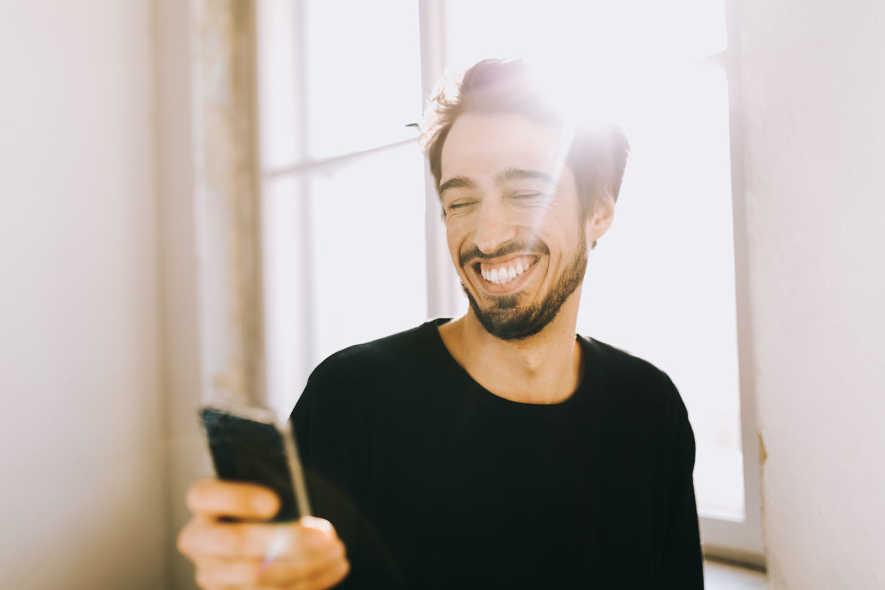 Happy young man using phone by window at home