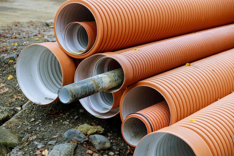 Stack of metallic pipes on land