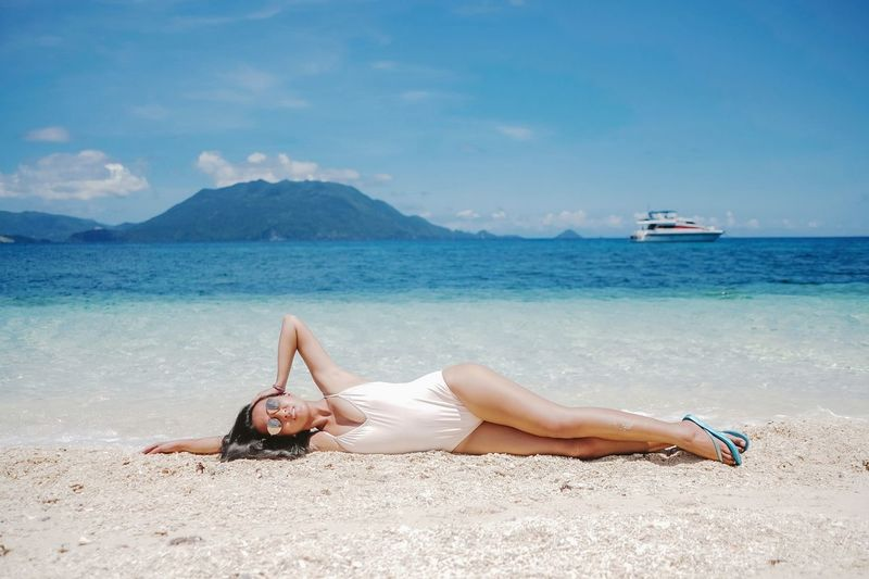 Young woman lying on beach against sky