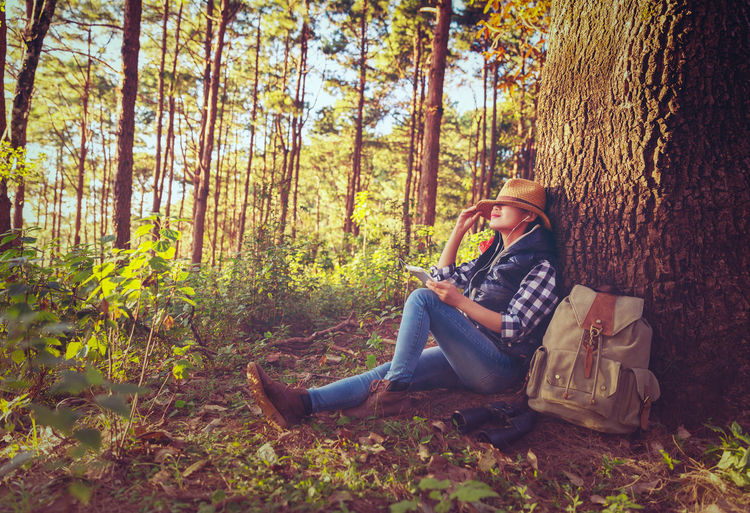 Young Woman Sitting By Tree Trunk In Forest
