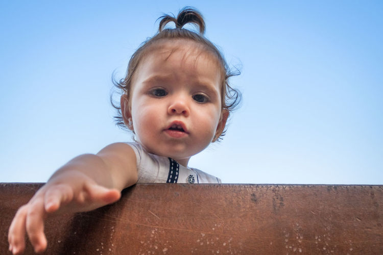 Low angle portrait of cute baby girl by retaining wall against clear sky