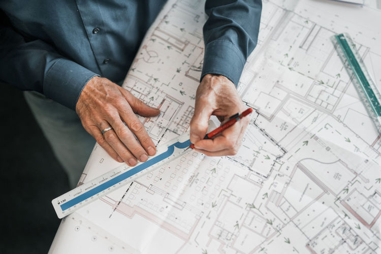 High angle view of man working on blueprint