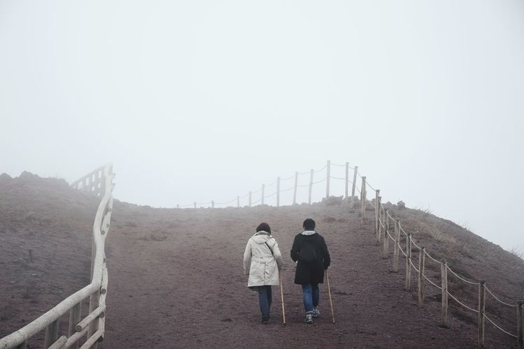 Rear view of hikers walking on field against sky during foggy weather