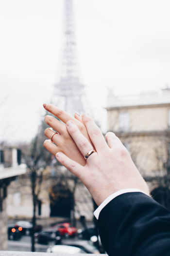 Close-up of couple hands against eiffel tower