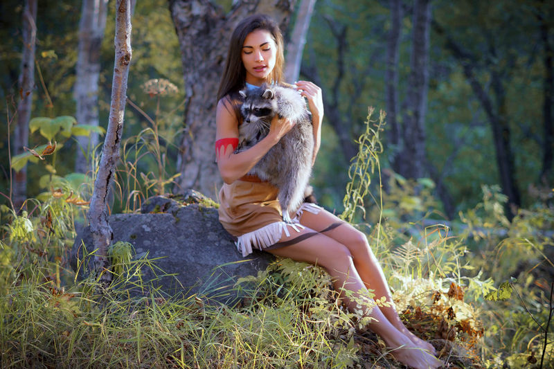 Smiling Young Woman In Traditional Clothing Sitting With Raccoon In Forest