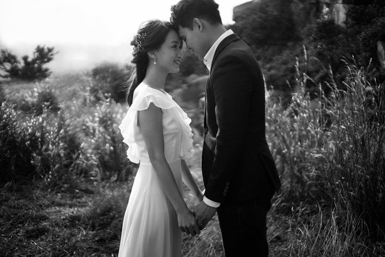 Side view of newlywed couple with face to face standing in park