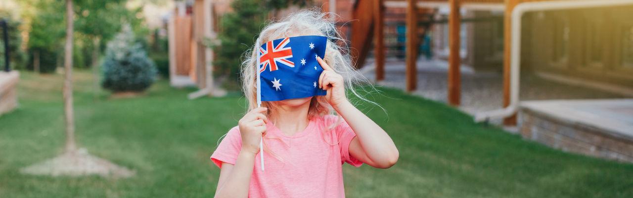 Cute girl holding australian flag at lawn