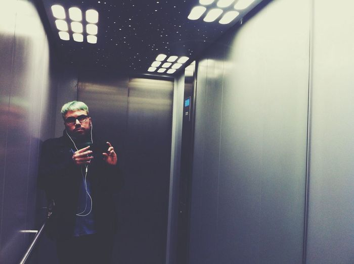 Young man listening to MP3 player in elevator