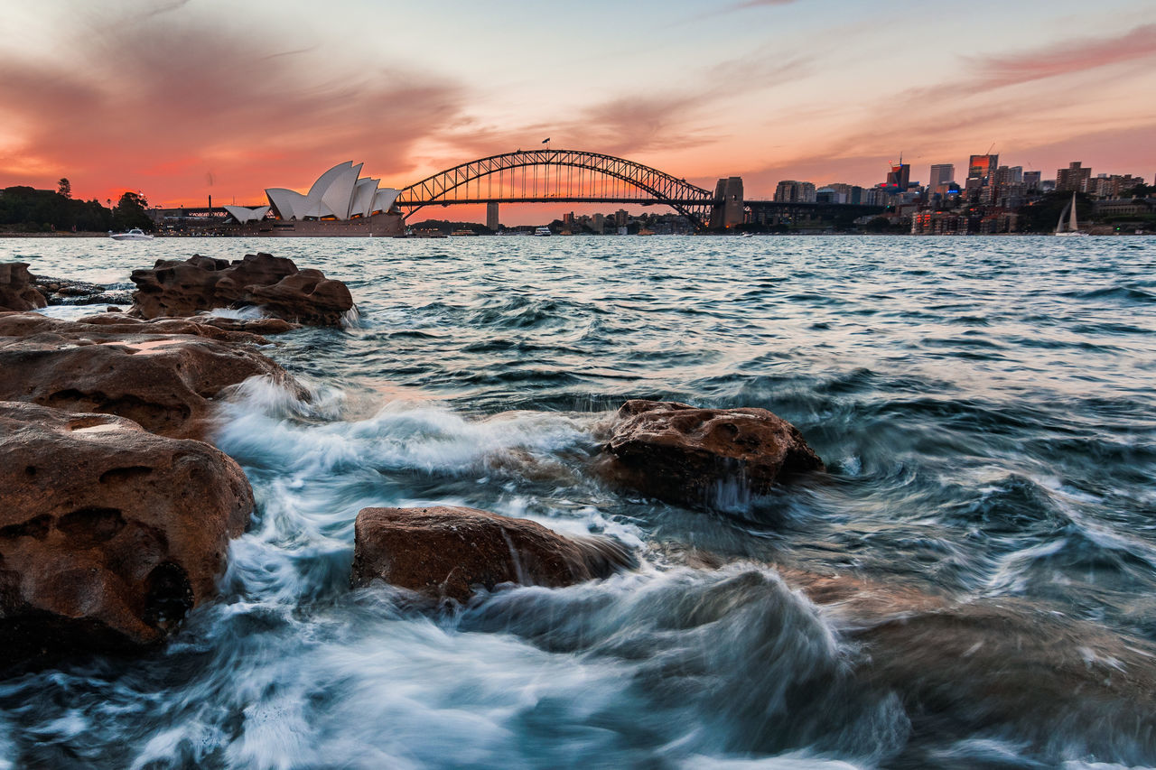 water, sunset, sky, built structure, architecture, sea, motion, rock, bridge, rock - object, connection, bridge - man made structure, nature, cloud - sky, beauty in nature, solid, scenics - nature, no people, building exterior, outdoors, bay