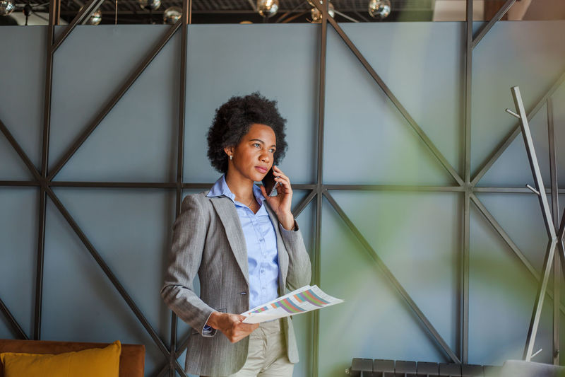 Businesswoman talking on mobile phone while holding graph